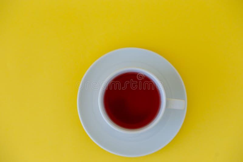 Tasse Tee auf einer Draufsicht des gelben Hintergrundes stockbild