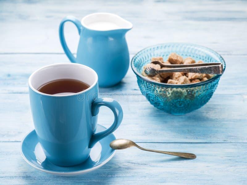 Tasse Tee, Milchkrug und Rohrzuckerwürfel stockfoto