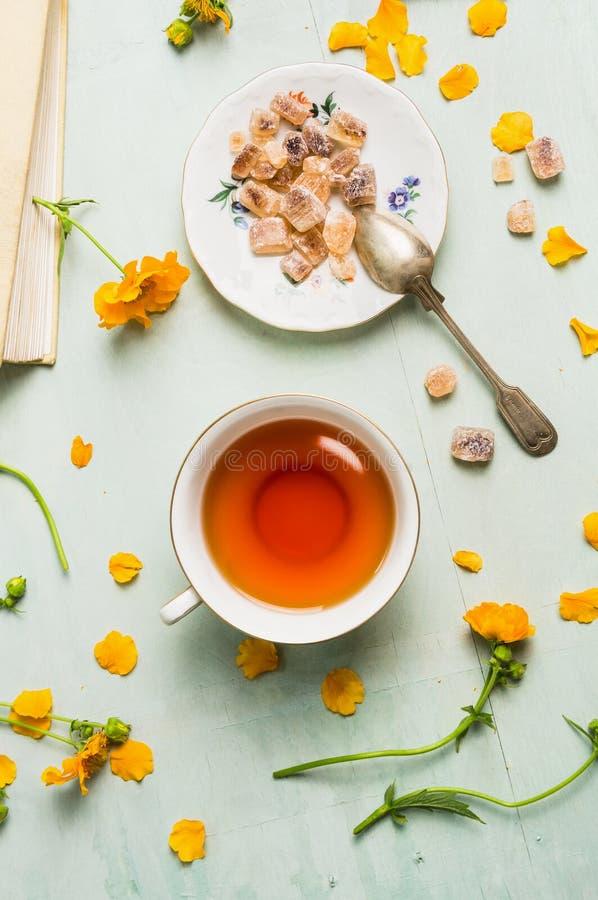 Tasse Tee mit braunem candi Zucker und Blumen stockfotos