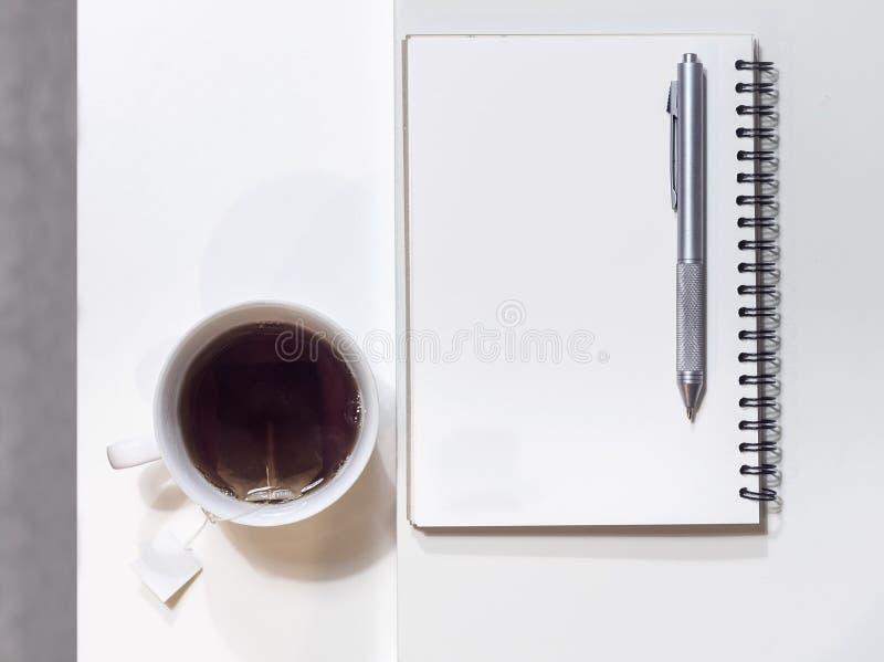 Tasse Tee mit Buch und Stift auf Tabelle lizenzfreie stockbilder