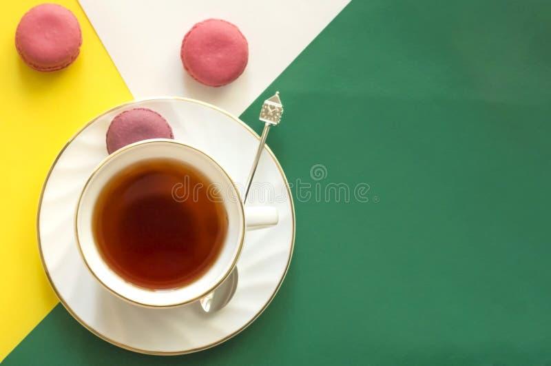 Tasse Tee mit buntem Mandelgebäck auf abstraktem gelbgrünem Hintergrund mit Kopienraum lizenzfreie stockfotos