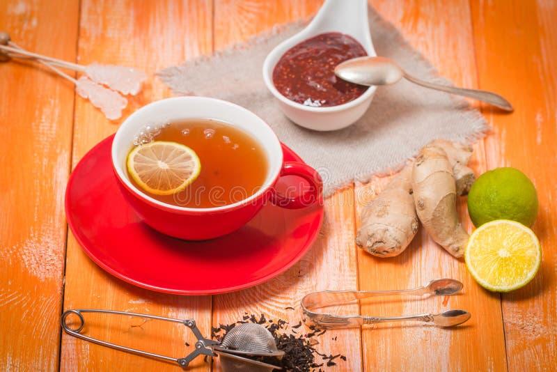 Tasse Tee mit Ingwer, Himbeermarmelade und Zitrone stockbild