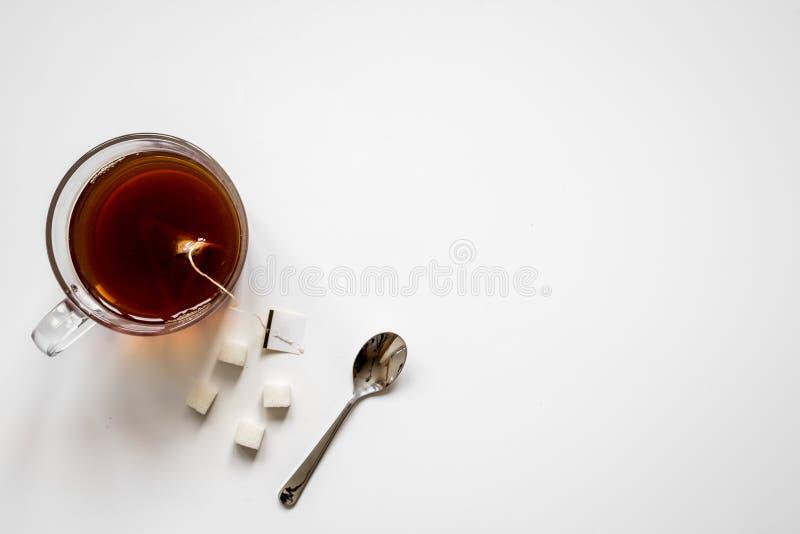 Tasse Tee mit Klumpen des Zuckerdraufsichtspotts oben lizenzfreies stockbild