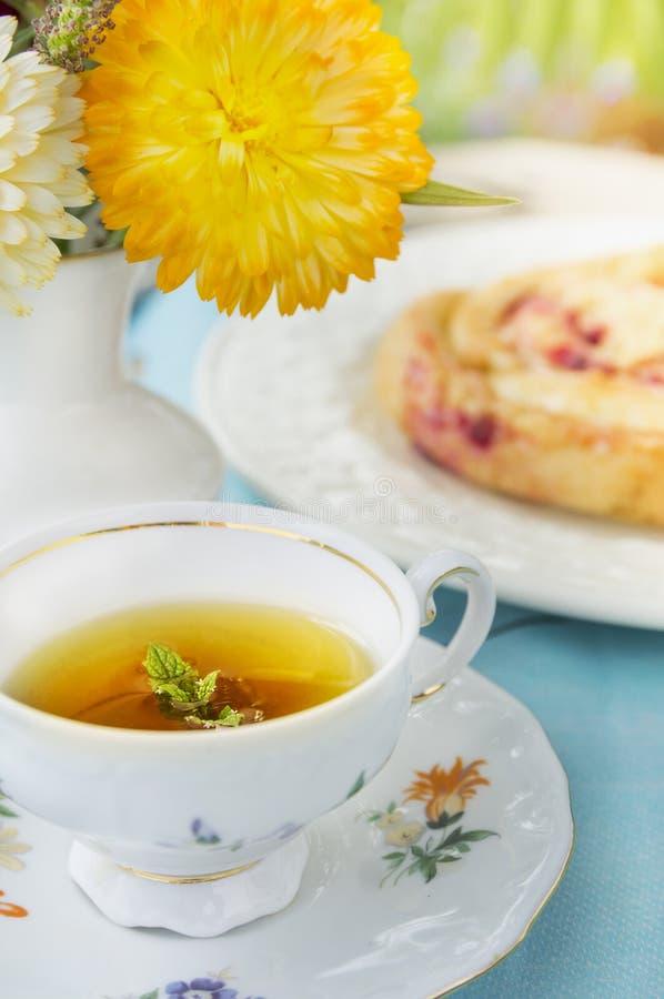 Tasse Tee mit Minze auf Hintergrund des Kuchens und der Blumen stockbild