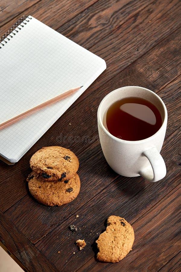 Tasse Tee mit Plätzchen, Arbeitsbuch und einem Bleistift auf einem hölzernen Hintergrund, Draufsicht stockfotos