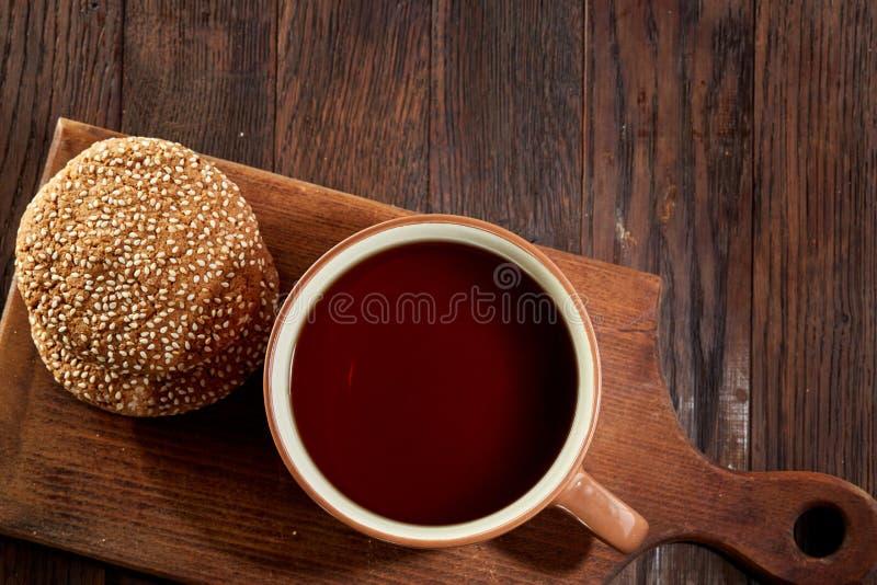 Tasse Tee mit Plätzchen, Arbeitsbuch und einem Bleistift auf einem hölzernen Hintergrund, Draufsicht stockfoto