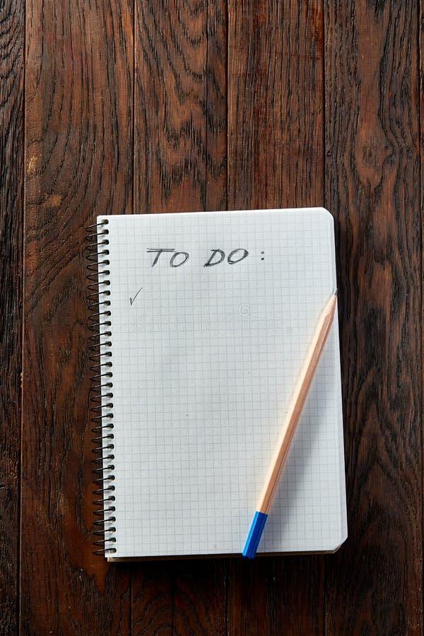 Tasse Tee mit Plätzchen, Arbeitsbuch und einem Bleistift auf einem hölzernen Hintergrund, Draufsicht lizenzfreie stockfotografie