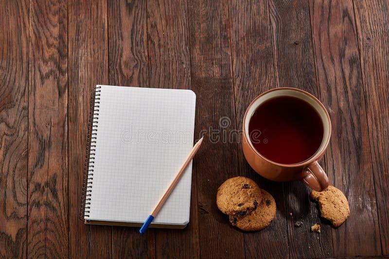Tasse Tee mit Plätzchen, Arbeitsbuch und einem Bleistift auf einem hölzernen Hintergrund, Draufsicht stockbilder