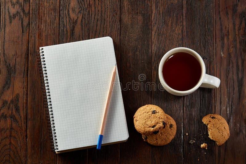 Tasse Tee mit Plätzchen, Arbeitsbuch und einem Bleistift auf einem hölzernen Hintergrund, Draufsicht stockfotografie