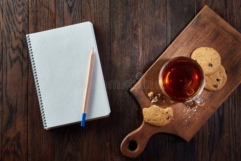 Tasse Tee mit Plätzchen, Arbeitsbuch und einem Bleistift auf einem hölzernen Hintergrund, Draufsicht stockbild