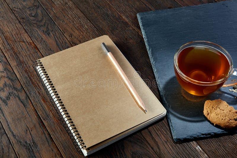 Tasse Tee mit Plätzchen, Arbeitsbuch und einem Bleistift auf einem hölzernen Hintergrund, Draufsicht lizenzfreies stockbild