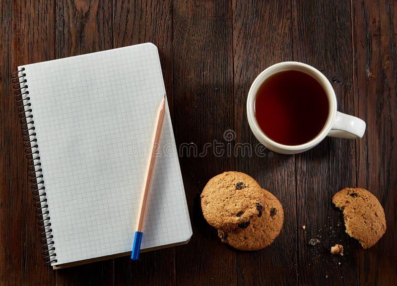 Tasse Tee mit Plätzchen, Arbeitsbuch und einem Bleistift auf einem hölzernen Hintergrund, Draufsicht lizenzfreie stockfotos