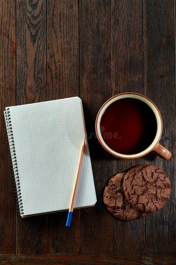 Tasse Tee mit Plätzchen, Arbeitsbuch und einem Bleistift auf einem hölzernen Hintergrund, Draufsicht, vertikal lizenzfreies stockfoto