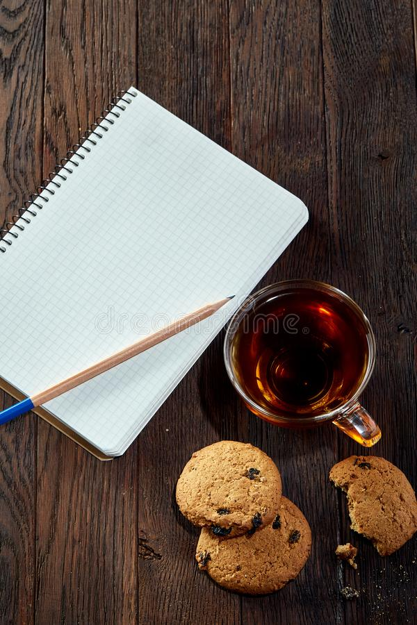 Tasse Tee mit Plätzchen, Arbeitsbuch und einem Bleistift auf einem hölzernen Hintergrund, Draufsicht, vertikal lizenzfreie stockfotografie
