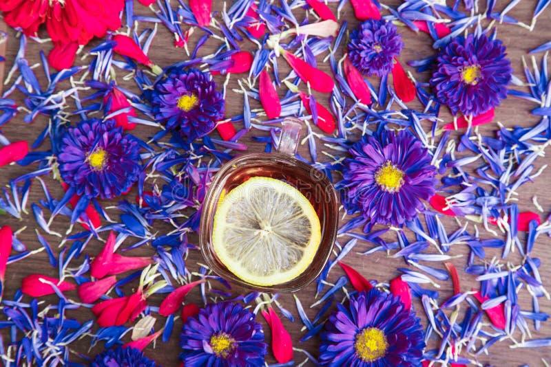 Tasse Tee mit Zitrone mit blauen Blumen stockbild