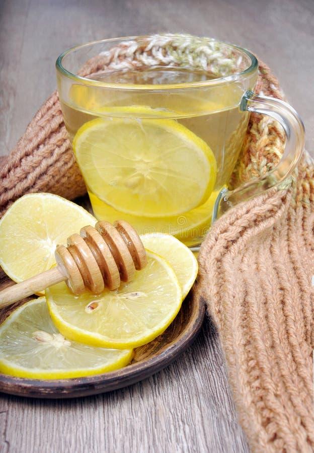 Tasse Tee mit Zitrone und einem warmen Schal Vitamintee Kälte- und Grippehilfsmittel stockfotos