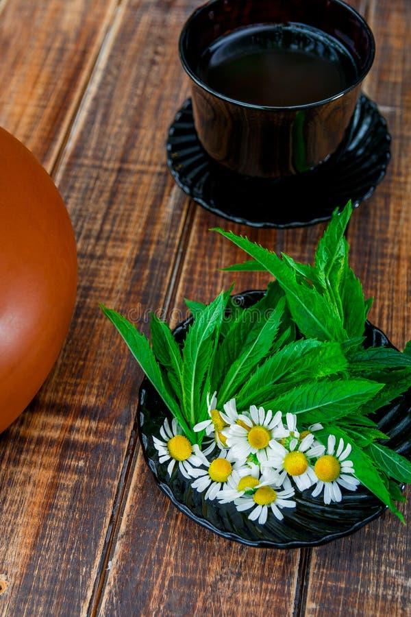 Tasse Tee nahe Schwarzblech mit frischer Minze lizenzfreie stockbilder