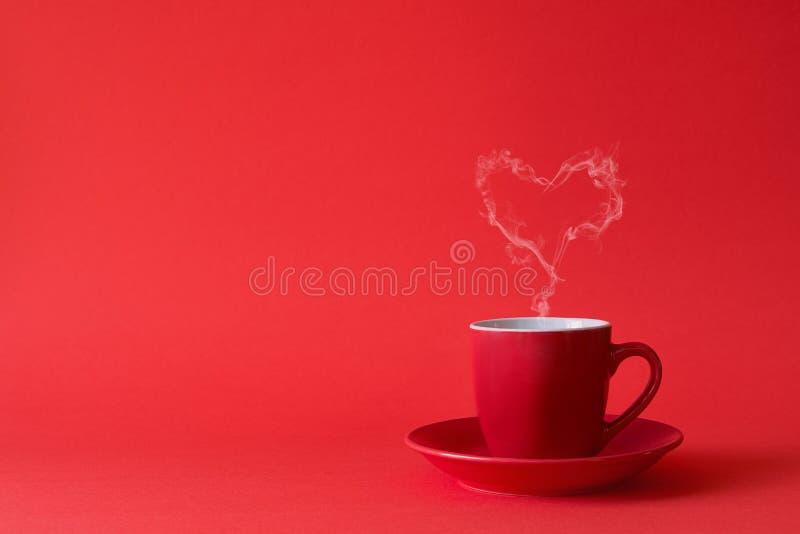Tasse Tee oder Kaffee mit Dampf in einer Herzform auf rotem Hintergrund Valentinstagfeier oder Liebeskonzept Kopieren Sie Platz lizenzfreie stockfotografie