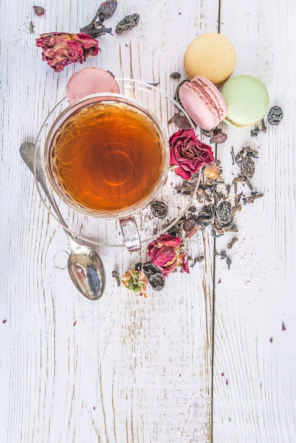 Tasse Tee, trockener rosafarbener Knopf, französische Makronen auf dem weißen hölzernen Hintergrund stockbild
