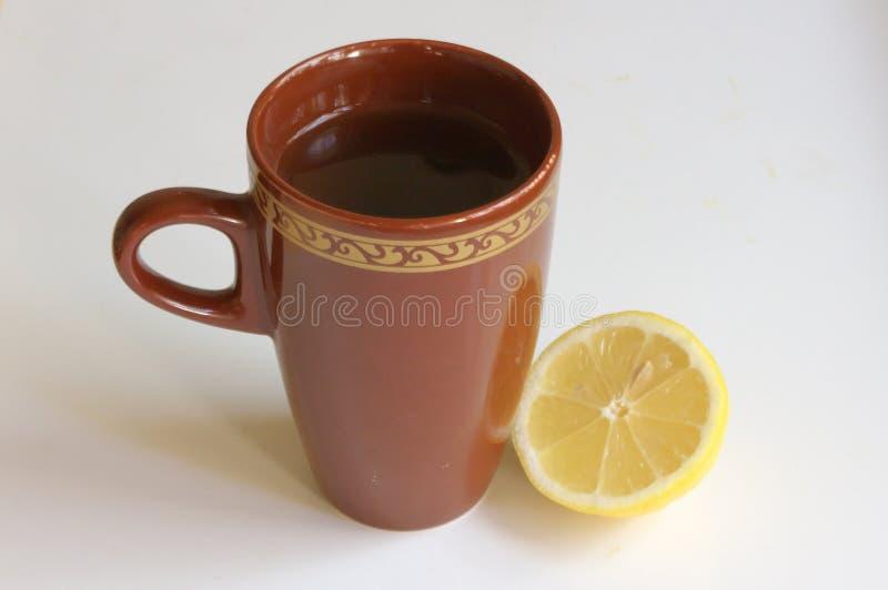 Tasse Tee und eine Zitrone stockbilder