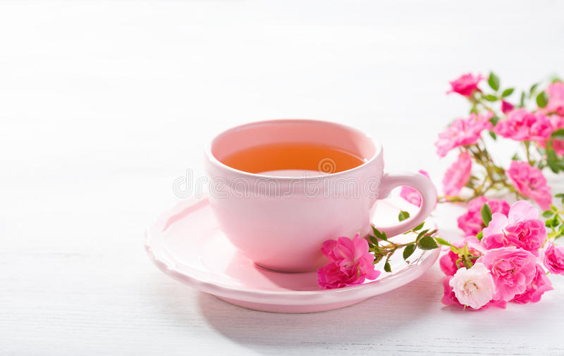 Tasse Tee und Niederlassung von kleinen rosa Rosen stockfotos
