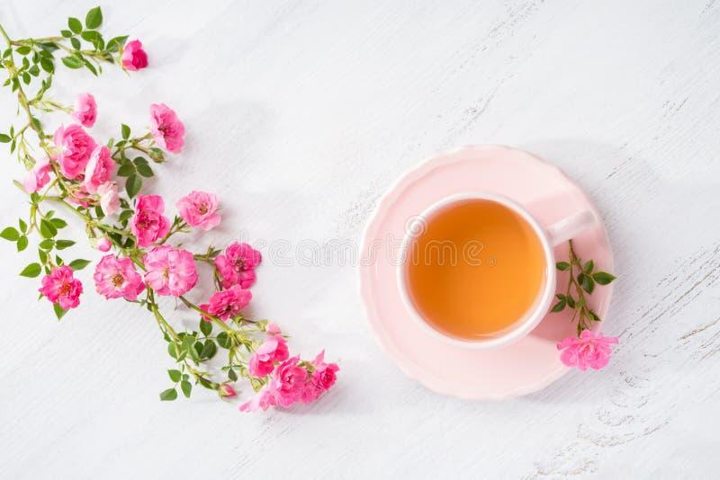 Tasse Tee und Niederlassung von kleinen rosa Rosen auf rustikaler Tabelle Flache Lage stockbild