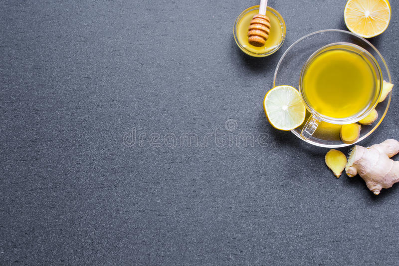 Tasse transparente de thé naturel vert avec du gingembre, le citron et la pierre à aiguiser photos stock