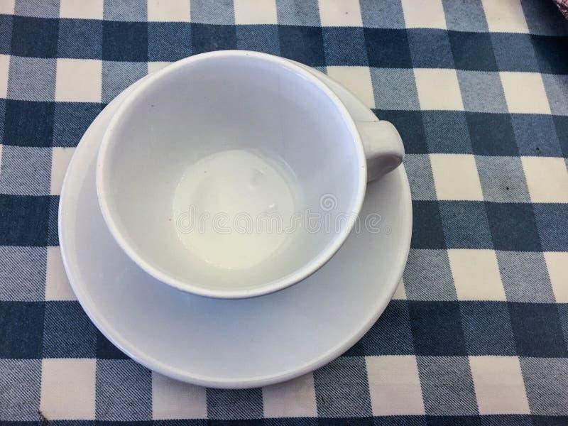 Tasse vide blanche et tablecloath bleu image libre de droits