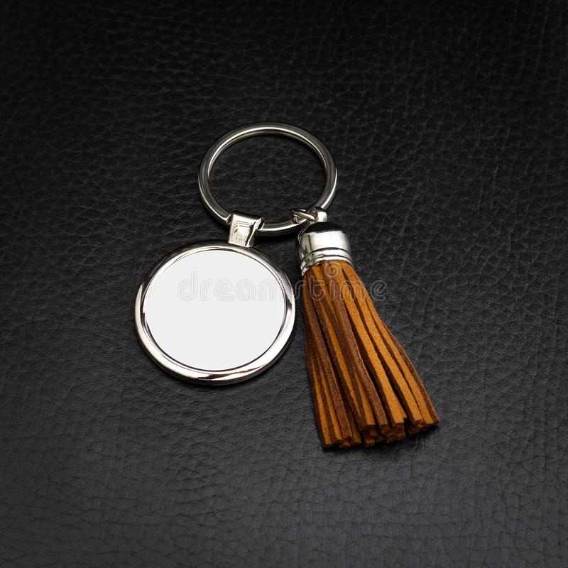 Tassel key ring on black leather background. Fashion leather key chain for decoration. Tassel key ring on black leather background. Fashion leather key chain stock image