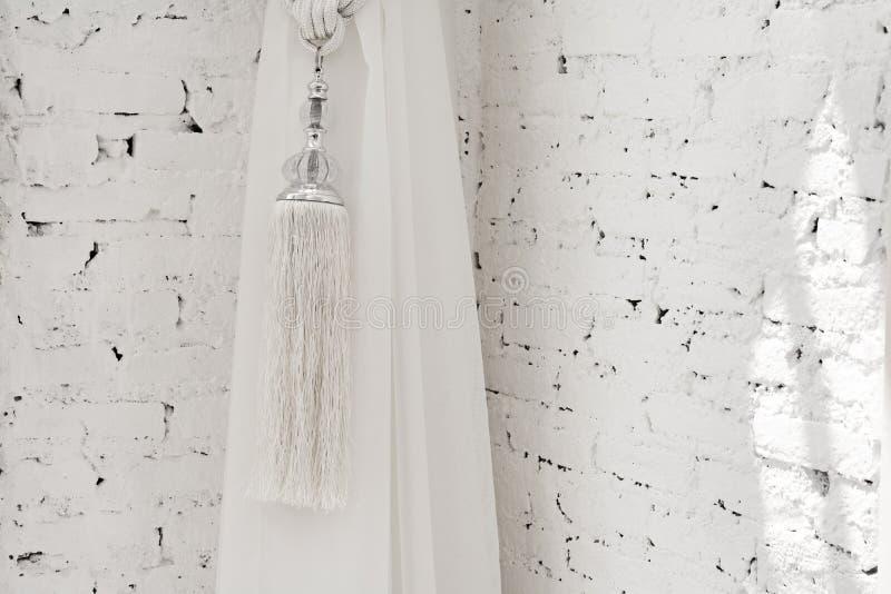 Tassels of curtain on white brick background stock photo