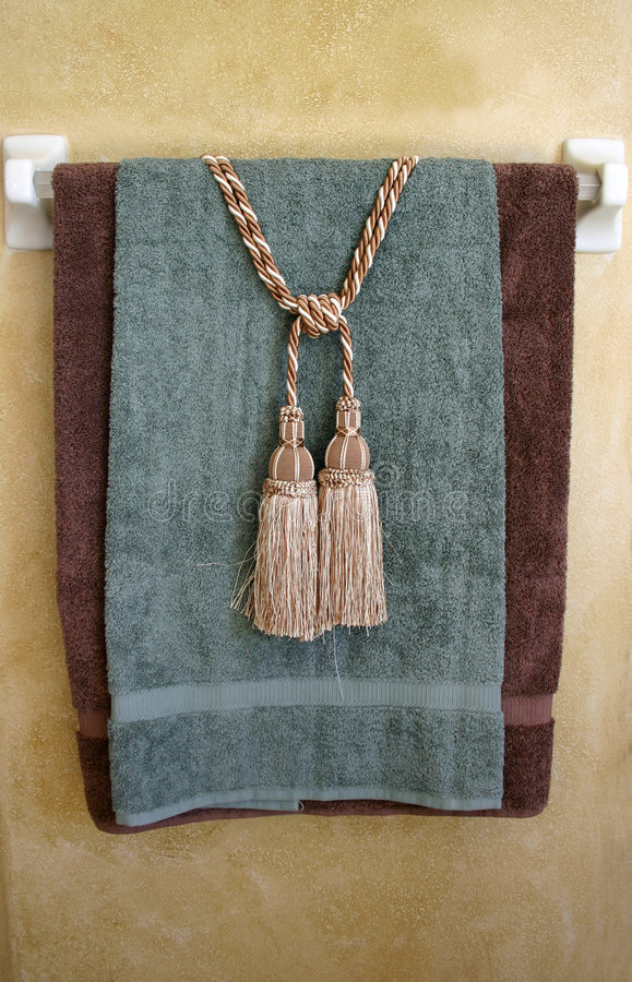 Tassels and Towels. Sage green and brown towels with tassels on white towel rack royalty free stock images