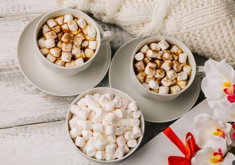 Tasses avec du café ou cacao et guimauves chauds, boîte-cadeau avec le ruban rouge, photographie stock