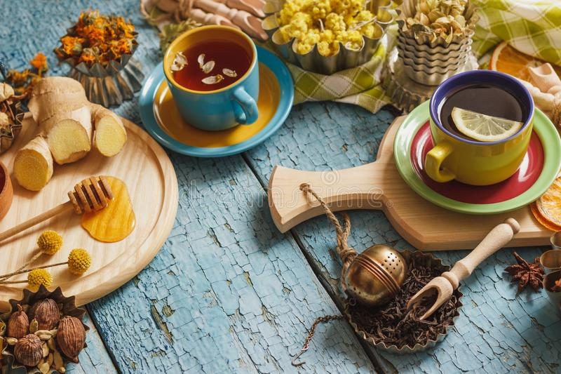 Tasses avec la tisane et les morceaux de citron, d'herbes sèches et de différentes décorations photos libres de droits