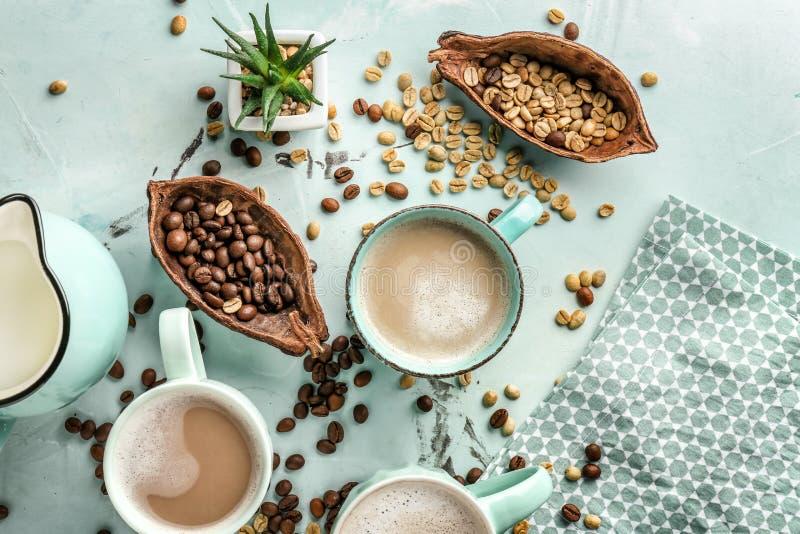 Tasses de café aromatique savoureux avec la cruche de lait et de haricots sur la table légère photos stock