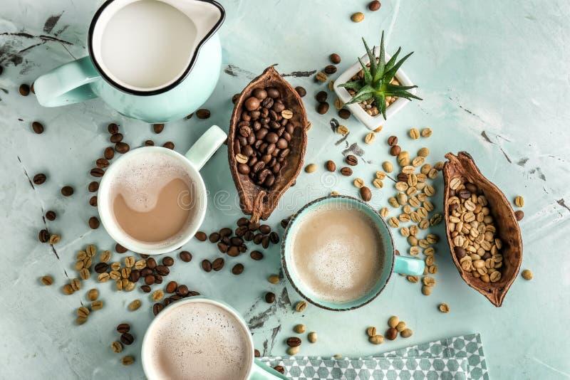 Tasses de café aromatique savoureux avec la cruche de lait et de haricots sur la table légère images libres de droits