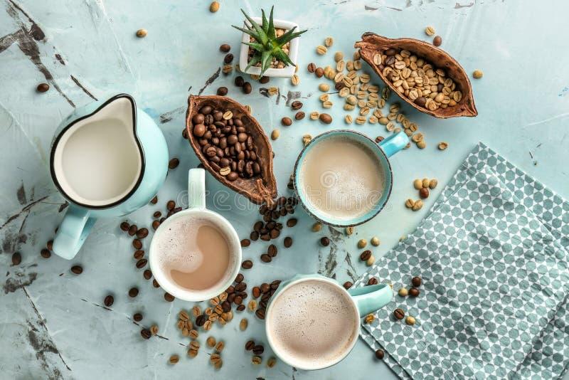 Tasses de café aromatique savoureux avec la cruche de lait et de haricots sur la table légère images stock