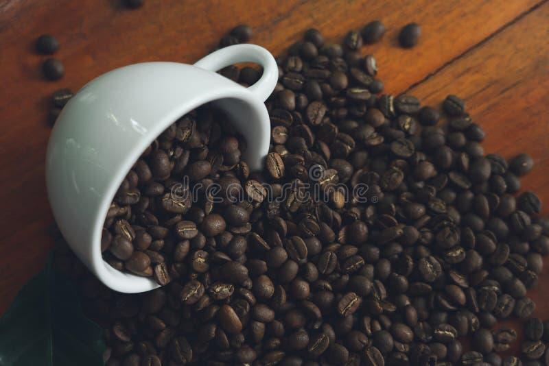 Tasses de café blanc et grains de café versés sur une table en bois, admirablement disposé, décorée des feuilles de café Est un m photographie stock libre de droits