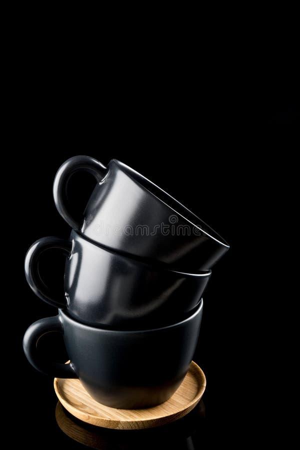 Tasses de café empilées, trois tasses modernes foncées empilées sur un plateau en bois, short d'angle gentil d'isolement sur le n images stock