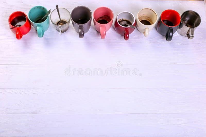 Tasses de café sales vides de différentes couleurs sur la table Concept de dopant de caféine, manque d'énergie et longue attente  photo libre de droits