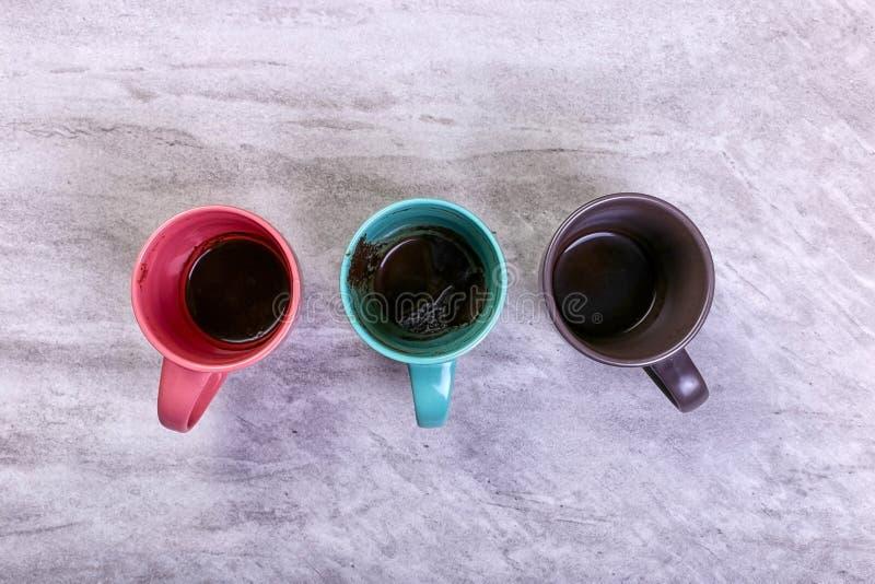Tasses de café sales vides de différentes couleurs sur la table Concept de dopant de caféine, manque d'énergie et longue attente  images stock