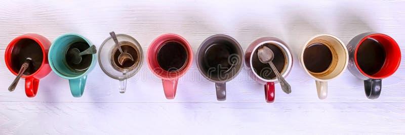 Tasses de café sales vides de différentes couleurs sur la table Concept de dopant de caféine, manque d'énergie et longue attente  photo stock