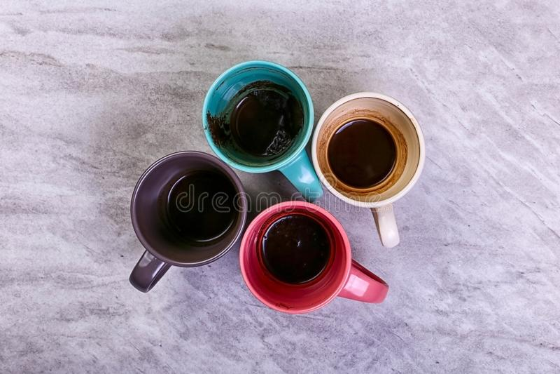 Tasses de café sales vides de différentes couleurs sur la table Concept de dopant de caféine, manque d'énergie et longue attente  photos stock