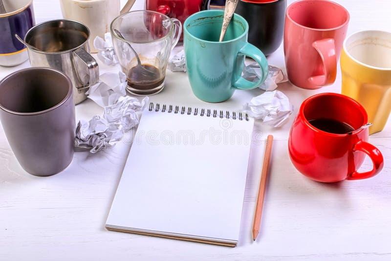 Tasses de café sales vides, différentes couleurs sur la table et un carnet pour écrire une lettre Dopant de caféine de concept, m photographie stock