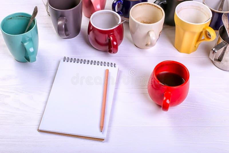 Tasses de café sales vides, différentes couleurs sur la table et un carnet pour écrire une lettre Dopant de caféine de concept, m image stock