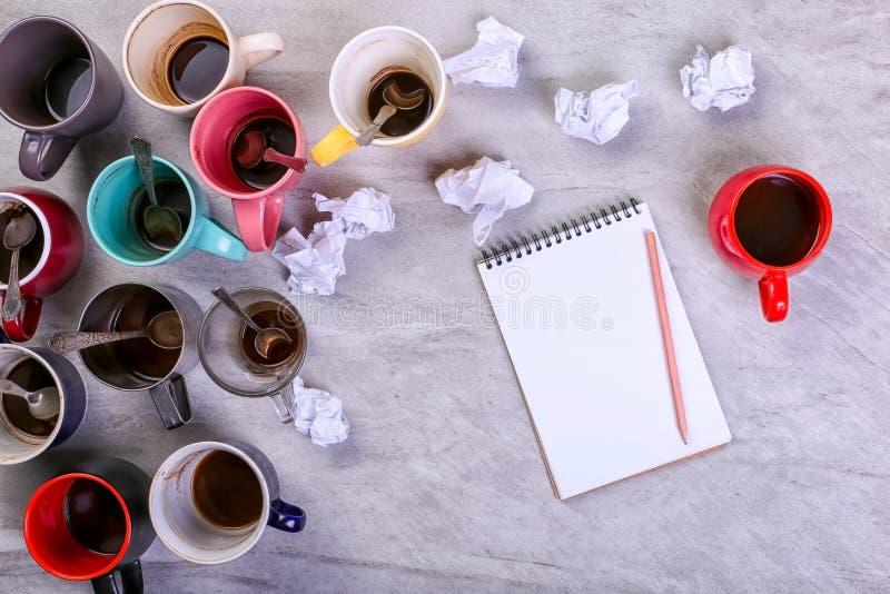 Tasses de café sales vides, différentes couleurs sur la table et un carnet pour écrire une lettre Dopant de caféine de concept, m images stock