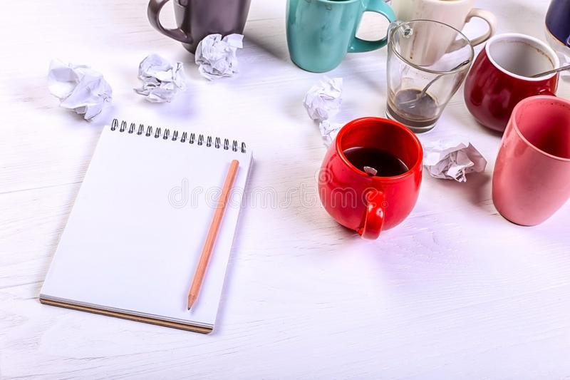 Tasses de café sales vides, différentes couleurs sur la table et un carnet pour écrire une lettre Dopant de caféine de concept, m photos stock