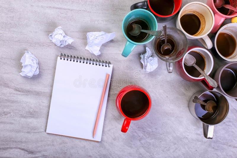 Tasses de café sales vides, différentes couleurs sur la table et un carnet pour écrire une lettre Dopant de caféine de concept, m photo stock