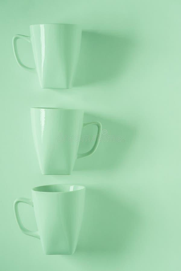 3 tasses de café vertes sur le fond vert dans une rangée verticale avec le copyspace vide photos stock