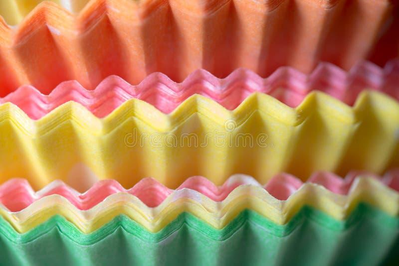 Tasses de cuisson de papier multicolores pour des petits gâteaux ou des petits pains photo libre de droits