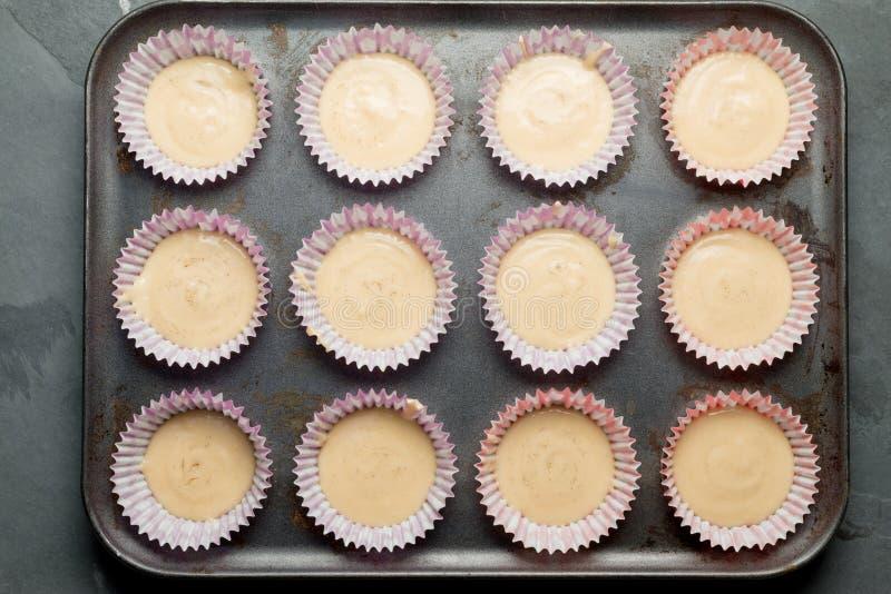 Tasses de petit pain avec la pâte lisse de gâteau dans le plateau de cuisson photo stock